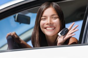 Teen sitting in drivers seat of a car holding keys.